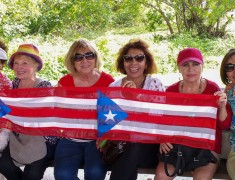 Group photo of NACOPRW Miami members, holding a Puerto Rican flag banner